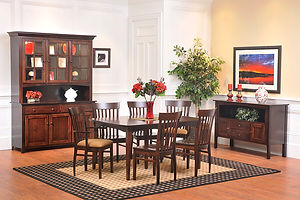 Lexington Shaker Amish Dining Room Furniture. Hidden leaf table with Shaker tapered legs, arched aprons, and boat-shaped top. Four side chairs with vertical back slats and wood seats plus two matched arm chairs with upholstered seats. Sideboard with two doors with square flat panels, two drawers, and an arched open space. China cabinet with three wood doors with square flat panels, two drawers, arched opening above the buffet top, and three top doors with mullions and beveled glass. All in brown maple with round wood knobs. Made in the USA.  Amish Dining Solutions