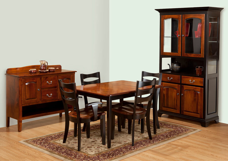 Millcreek solid brown maple dining room with dining table with michaels red stain on the top and onyx black stain on the legs and apron, two side chairs and two arm chairs in onyx black stain with michaels red seats, server with two doors and two drawers in red stain with nickel knobs and knocker pulls, open shelf neat bottom and curved gallery backsplash, and two-door china cabinet hutch with two doors and two drawers in bottom, open counter, and two doors with arched beveled glass in top, china cabinet is solid brown maple with onyx black stain and michaels red stain on doors and drawers. solid hardwood furniture made in the usa amish furniture pittsburgh mills
