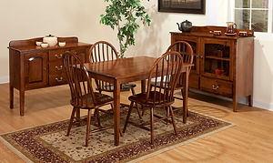 Millcreek Amish Dining Room Furniture Collection, with a rectangular table with four tapered square legs, four bow-back Windsor chairs with wood seats and stretcher bars, a sideboard with three drawers and two doors with arched raised panels and a scalloped backsplash, and a server with two drawers and two doors with arched glass panels and a scalloped backsplash, all shown in solid brown maple with michaels stain and brushed nickel knobs and pulls. Made in the USA.