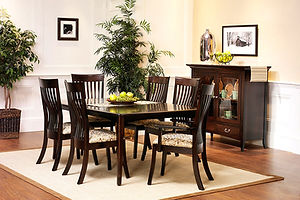 English Shaker Amish Dining Room Furniture Collection, four leg rectangle table with curved shaker legs and self-storing leaves. Six high-back shaker chairs with lumbar support and upholstered seats. Pottery pantry with two drawers and two doors with arched beveled glass panels. All shown in brown maple with onyx stain with brushed nickel pulls. Solid Hardwood Furniture, Made in the USA. Amish Dining Solutions