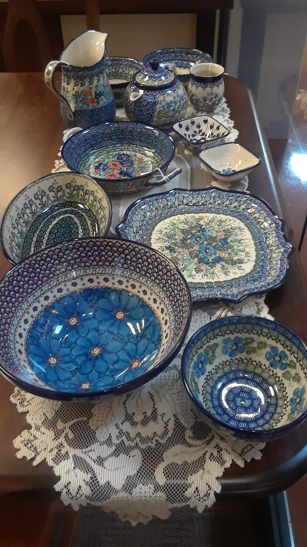"""Items Shown:  Pedestal Bowl - Morning Glory Pattern Nesting Bowl 9"""" - Blue Cosmo Unikat (U4) Pattern Serpentine Tray - Violet Delight Unikat (U930) Pattern Oval Baker 9.5"""" - Blue Spring Daisy Pattern Small Round Baker w/ Handles - U4090 Unikat (U930) Pattern Square Bowl 4"""" - Bleeding Heart Pattern Square Bowl 4"""" - Pattern 2150 Pattern Teapot 1qt - Bluebell Pattern Bubble Mug 8oz - Bluebell Pattern Pitcher 26oz - Pastel Unikat (U3) Pattern Soup/Salad Bowl - Daisy Garden (U930) Pattern Soup/Salad Bowl - Peacock Feather Pattern  Displayed on our Denver Double Pedestal Table, built in solid Rustic Cherry with Asbury stain"""