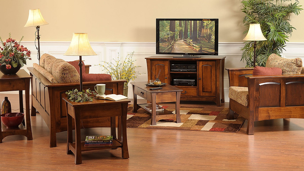 The Woodlands TV Stand is shown in brown maple with matching coffee table end table and sofa table