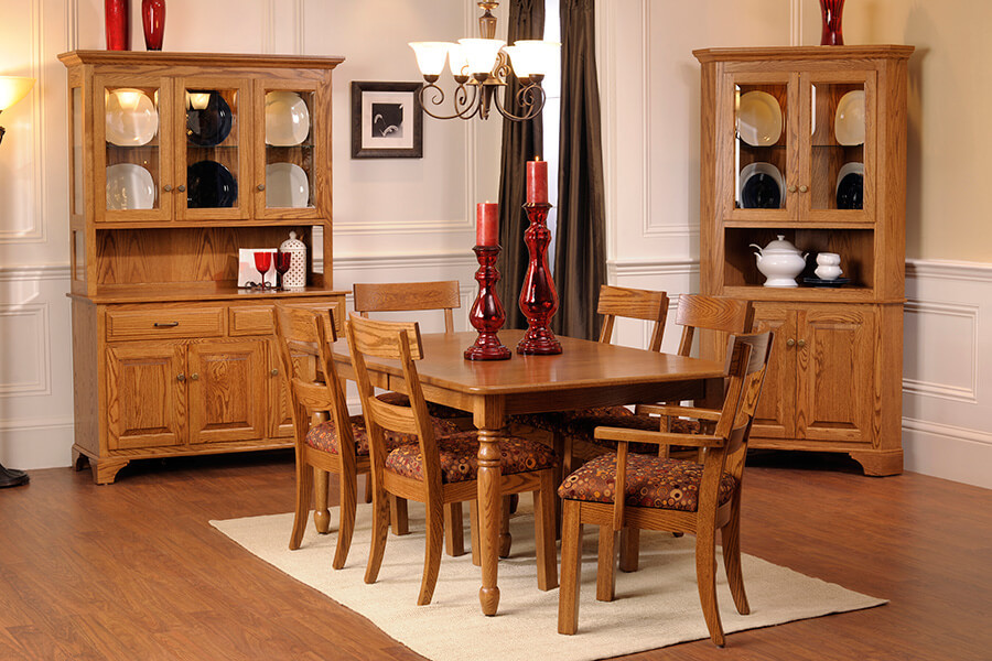 "Americana Dining Room featuring a 42""x66"" dining table with turned farmhouse legs and self-storing extension boards with six dining chairs with padded seats four side chairs two arm chairs shown with three-door china cabinet with two drawers LED lights on a touch switch and corner cabinet all built in solid oak with antique English hardware raised panel doors traditional molding traditional feet The Amish Home Amish Furniture Galleria at Pittsburgh Mills Made in the USA Hardwood Furniture Solid Oak Furniture"