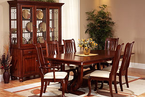 Hampton Amish Dining Room Furniture Collection, with trestle table with extension leaves. Four side chairs and two arm chairs with carved stiles and claw feet with upholstered seats. China cabinet with three wood doors with raised panels, three drawers, three glass doors, glass sides, bun feet, adjustable shelves, and touch-switch lighting. All shown in solid cherry with Washington stain and weathered nickel knobs and pulls. Made in the USA. Amish Dining Solutions