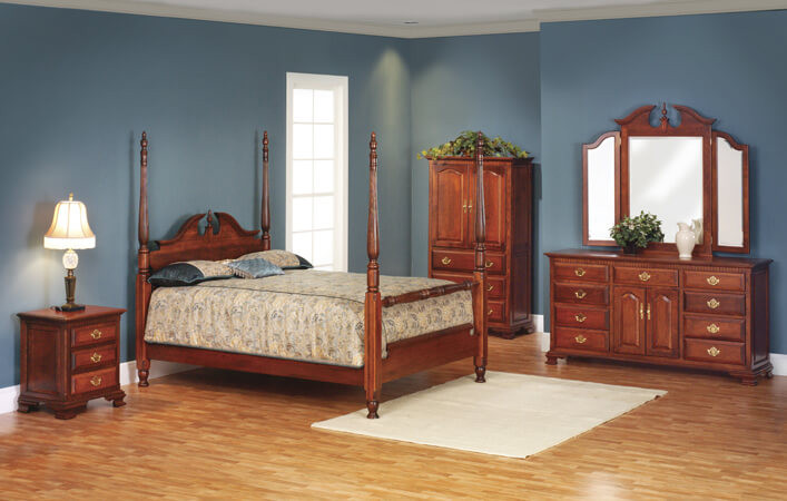 The Queen Anne Bedroom is shown in cherry and includes a queen poster bed, long dresser, tri-fold mirror, armoire, and 3 drawer nightstand
