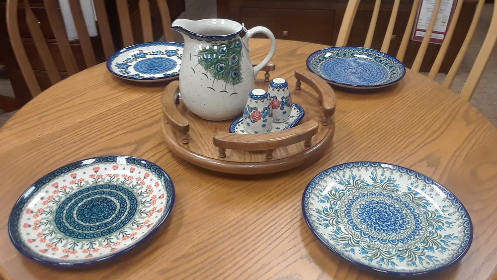 """Items Shown:  Dinner Plate 10"""" - Blue Poppy Pattern Dinner Plate 10"""" - Peacock Feather Pattern Dinner Plate 10"""" - Bluebell Pattern Dinner Plate 10"""" - Peach Spring Daisy Pattern Pitcher 2qt - Art of the Feather Pattern Salt & Pepper - 4th of July Pattern Lazy Susan 14"""" – Oak with fruitwood stain  Shown on our Wheatland Round Dining Table, built in red oak with seely stain"""