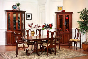 Queen Victoria Amish Dining Room Furniture. Cherry dining table with double reeded pedestal base and cabriole feet. Six fiddle back chairs with cabriole legs and upholstered seats. Corner china cabinet with two wood doors with square raised panels and upper doors with beveled glass, with adjustable glass shelves and a touch-switch light. Canted china cabinet with four wood doors with square raised panels, one drawer, and four upper doors with beveled glass, with adjustable glass shelves and a touch-switch light. All shown in solid cherry with Washington stain and brass knocker pulls and brass knobs with punched back pieces. Classic Queen Anne Furniture. Made in the USA. Amish Dining Solutions