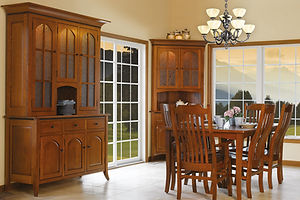 Bunker Hill Amish Dining Room Furniture. Extension table with self storing leaves, four curved tapered legs. Four side chairs and two arm chairs with lumbar support. Corner cabinet with two doors with arched raised wood panels, two doors with seeded glass, adjustable shelves, and touch-switch lighting. China cabinet with three doors with arched raised wood panels, three drawers, three doors with seeded glass, adjustable shelves, and touch-switch lighting, with rope twist accent, painted black.  All shown in solid quartersawn white oak with michaels stain, black iron knobs. Made in the USA.