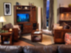 Urban Living Room Furniture Collection|Contemporary clean style. Wood-framed sofa, chair, and loveseat with modern flush panel design, block feet, and top-grain leather cushions with throw pillows. Shown with matching entertainment center, base has two doors, two drawers, and flip-up speaker door with speaker cloth, top has two glass doors, one wood door with adjustable shelves, satin nickel bar pull hardware. Matching coffee table and end table have block legs and plinth bases.|Solid Brown Maple in Rich Tobacco OCS228|The Amish Home|Amish Furniture at the Pittsburgh Mills