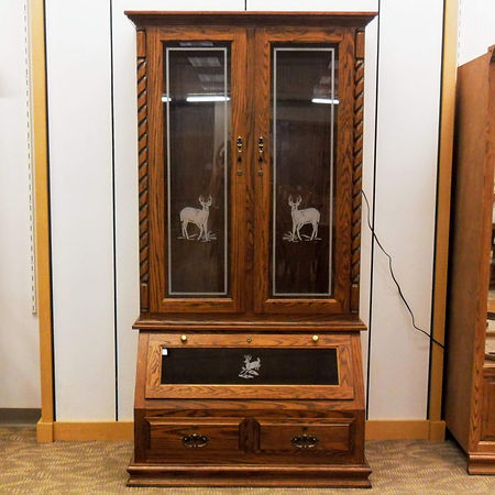 Floor Model Special 8-Gun Cabinet with Etched Glass Classic style with traditional crown molding and base trim, rope twist accent. Two tall glass doors with deer etched design. Wood back, burgundy velvet accents, LED touch light. Lower drop-down door with deer etched design, two dovetail drawers. Antique English Hardware, locks on add doors & drawers. Solid Oak in Michaels OCS113 41 1/2in W x 22in D x 77 1/2in H Made in the USA Solid Hardwood Furniture Made in the USA The Amish Home Furniture in Pittsburgh Mills