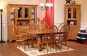Americana Amish Dining Room Furniture Collection, double pedestal table with leaves underneath. Four side chairs and 2 arm chairs with sheaf backs, turned legs, stretcher bars, and wood seats. Corner china cabinet with two wood raised panel doors, two beveled glass doors, adjustable shelves, and touch-switch lighting. Country china cabinet with four wood doors with raised panels, four glass doors, one drawer, glass sides, adjustable shelves, and touch-switch lighting. All shown in solid red oak with seely stain and brass knobs and pulls. Made in the USA. Amish Dining Solutions