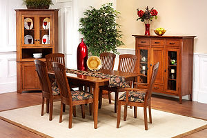 Newport Shaker Amish Dining Room Furniture Collection, with a rectangular table with self-store extension boards with four tapered square legs. Four side chairs and two arm chairs with arched top rails, vertical slats with lumbar support, and upholstered seats. Corner cabinet with two wood doors with square flat panels on the bottom, two glass doors on the top, open buffet area. Dutch pantry with four drawers, one wood door with square flat panel between two glass doors. All in solid quartersawn white oak with michaels stain and black iron knobs and pulls. Made in the USA.
