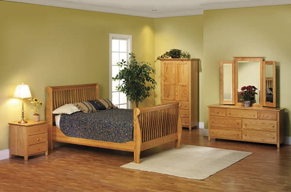 The Pittsfield Shaker Bedroom is shown in oak and includes a queen  slat bed, double dresser, tri-fold mirror, armoire, and 3 drawer nightstand