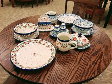 "Butter Dish - Orange Poppies   Salt & Pepper - Flowery Vines   Napkin Holder - Cherry Jubilee   Nesting Bowl 6.5"" (4pc setting) - White Pansy   Bubble Mug 16oz (4pc setting) - White Pansy   Plate 7.75""  (4pc setting) - White Pansy   Dinner Plate 10"" with hanger (4pc setting) - White Pansy   Nesting Bowl 6.5"" (4pc setting) - Simple Scarlet   Bubble Mug 16oz (4pc setting) - Simple Scarlet   Plate 7.75""  (4pc setting) - Simple Scarlet   Dinner Plate 10"" with hanger (4pc setting) - Simple Scarlet - Ceramika Artystyczna Bolesławiec Polish Pottery - The Amish Home - Galleria at Pittsburgh Mills Amish Furniture"