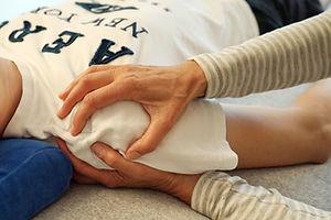 Die Therapeutin umfasst mit beiden Händen das Schultergelenk des liegenden Klienten. Sie beobachtet den Atem- und Craniosacral-Rhythmus und untersucht Beweglichkeit und Tonus des Schulterbereichs; Gelenkbeschwerden, Rheuma