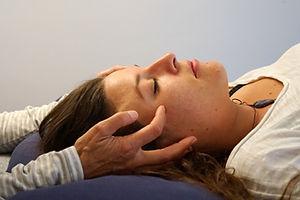 Der Kopf einer liegenden Frau wird seitlich mit den Händen der Therapeutin berührt. Sie ertastet den CRI und ein ev. Ungleichgewicht im Craniosacralen System; ausgleichend auf das vegetative Nervensystem.