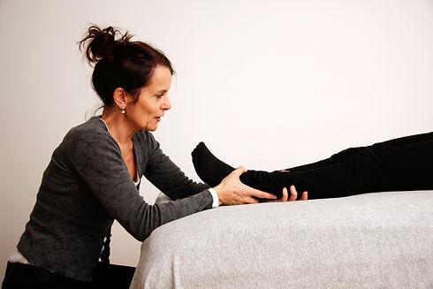 Die Therapeutin hält mir ihren Händen ein Fussgelenk der liegende Klientin, stimmuliert mit feinen Impulsen den Craniosacralen- sowie den Atem-Rhythmus.