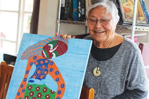 Pusi holds her latest, more abstract piece