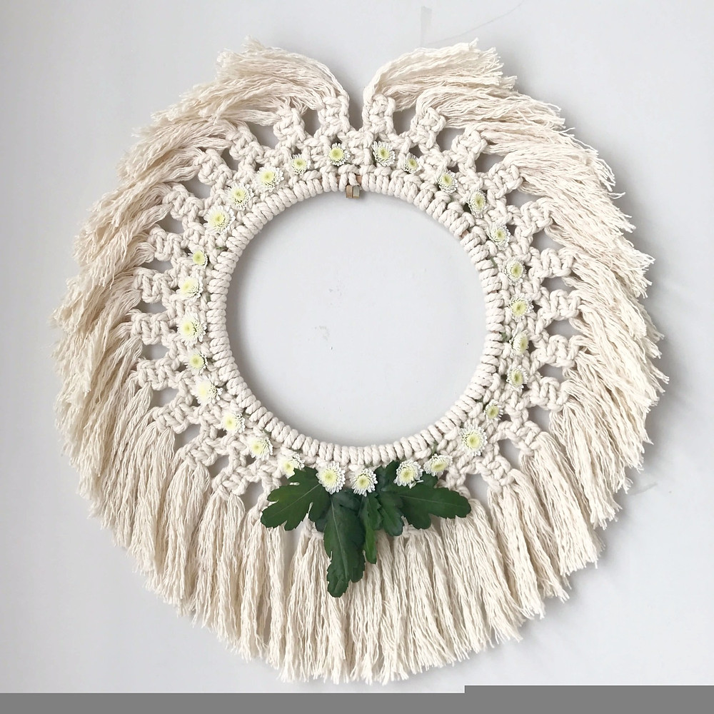 macrame wreath with daisies and leaves on the wall