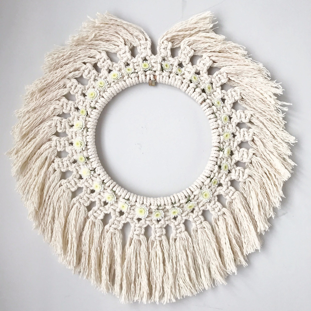 macrame wreath with daisies on the wall