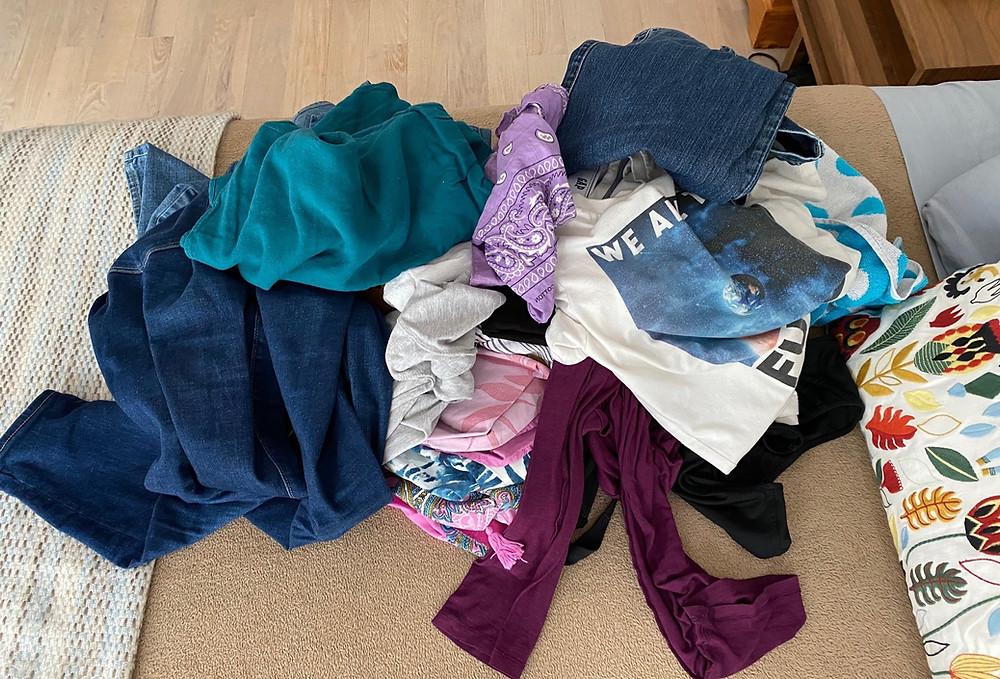 ropa amontonada sacada de la lavadora y lista para doblar y guardar