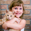 Little girl smiling, holding a ginger tabby cat