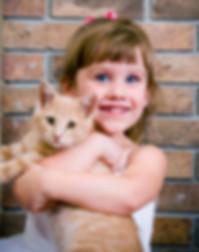 Little girl smiling, holding a ginger cat