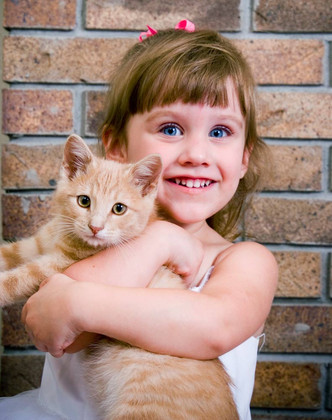 Little girl smiling, holding a ginger cat