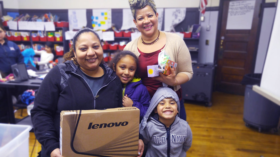 A Tech Goes Home instructor stands with a learner and her two children holding a new Chromebook