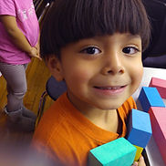A young child smiles at the camera.
