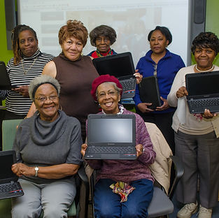 A group of women who are graduating from a TGH Community course hold up their new laptops.