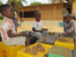 School children in africa making sand castles