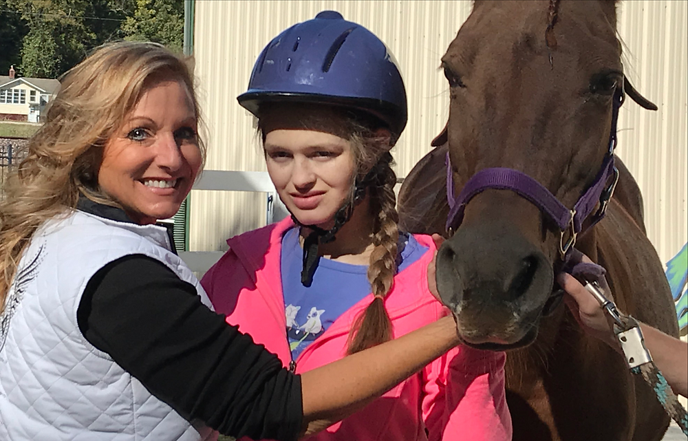 Ride On St. Louis volunteer Kami, participant Katelyn and horse Pharma pose after a session