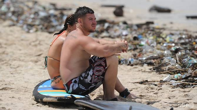 Tourists sit on a surfboard along Kuta beach, surrounded by debris and rubbish washed up by the tide Read more at https://www.strawmansg.com/blog/anti-plastic-straw-wave-has-struck-bali-as-government-bans-single-use-plastics