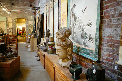 This is another image of the interior of the warehouse. In this image there are large stone buddhas, vases, hibachi, and tansu