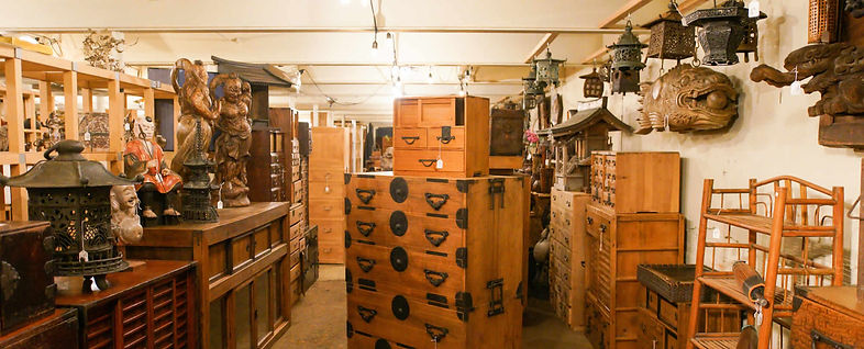 The image is of the interior of the Kyoto Art and Antiques Warehouse. In it you would see carvings, beautiful tansus with metalwork, old iron lanterns, and so much more.