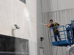 Man Pressure Washing Building on Lift Arm