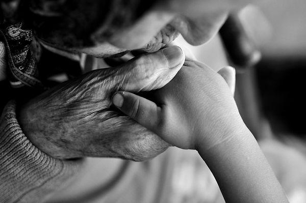 an elderly woman kissing children's hand
