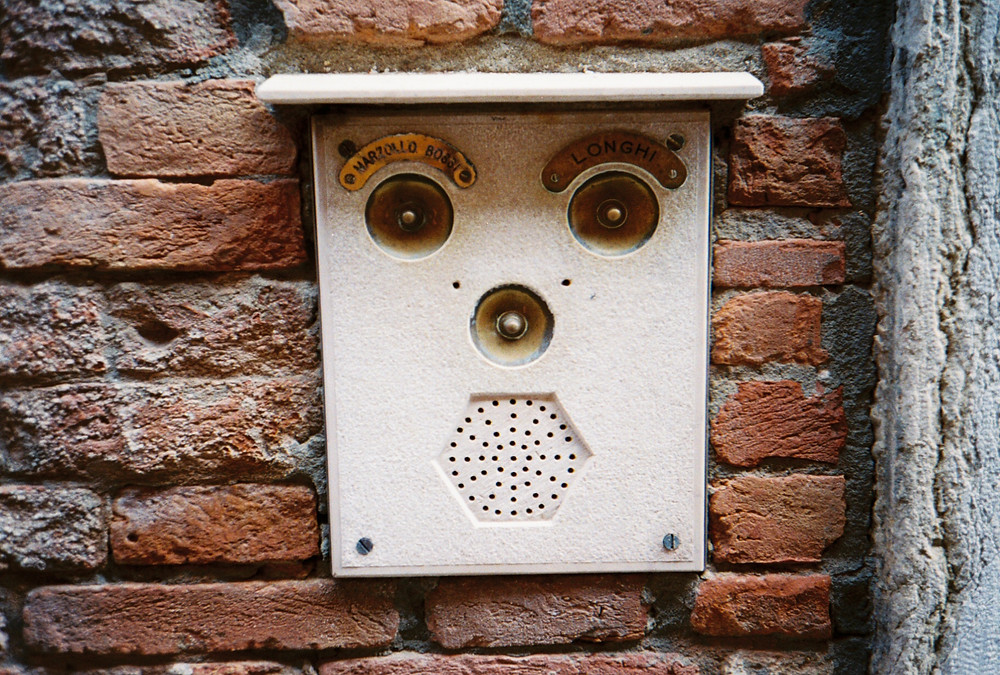 doorbell with face-like features mounted on a brick residential building