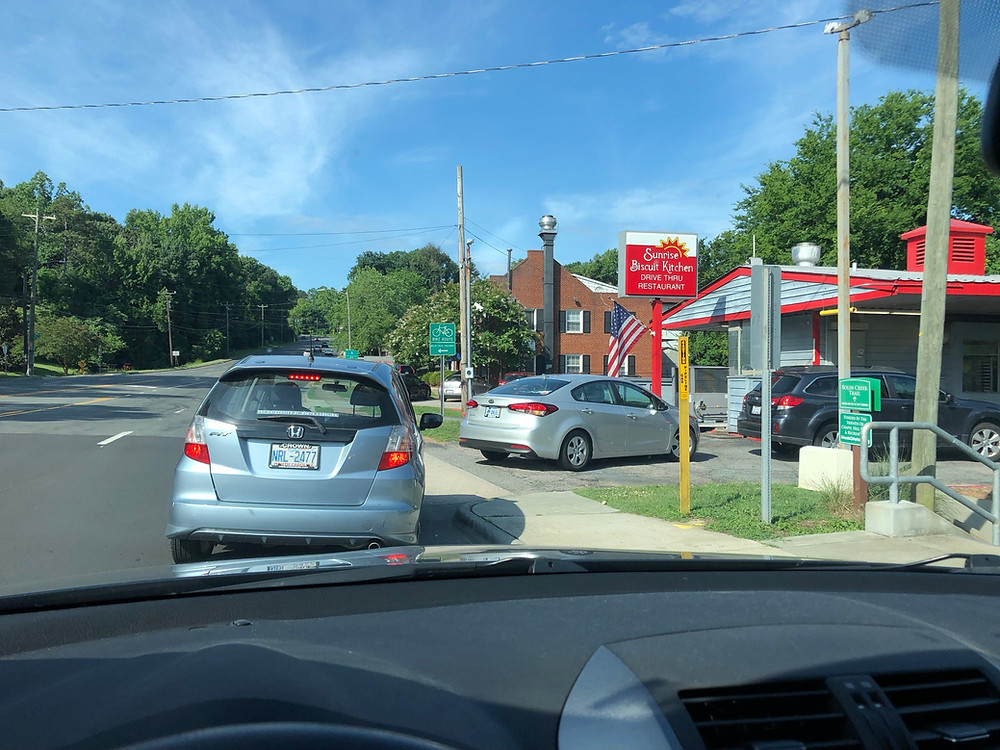 line of cars leading to Sunrise Biscuit Kitchen drive thru with blue sky in background