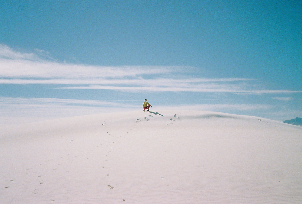 white woman seen from afar, posing on white sands with blue sky and clouds behind her
