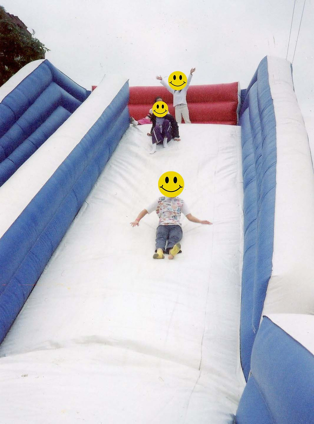 collage of three children going down an inflatable slide with smiley face stickers over their faces