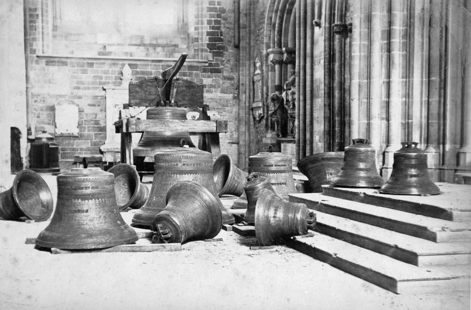 black and white photo of large church bells resting on the floor of a church's interior