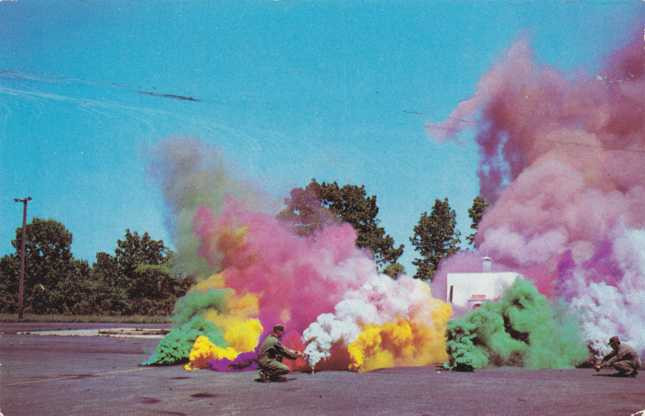 army men setting off colorful smoke bombs in a parking lot with blue sky and trees behind them