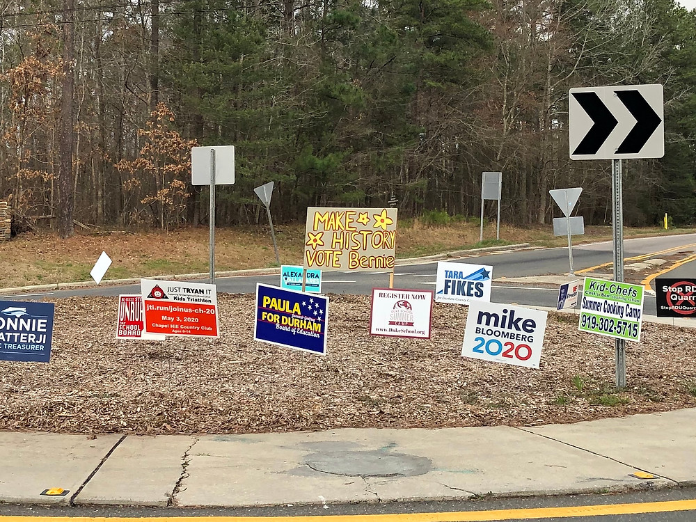 """2020 campaign signs in a traffic circle, including handmake """"Make History, Vote Bernie"""" sign with yellow flowers"""