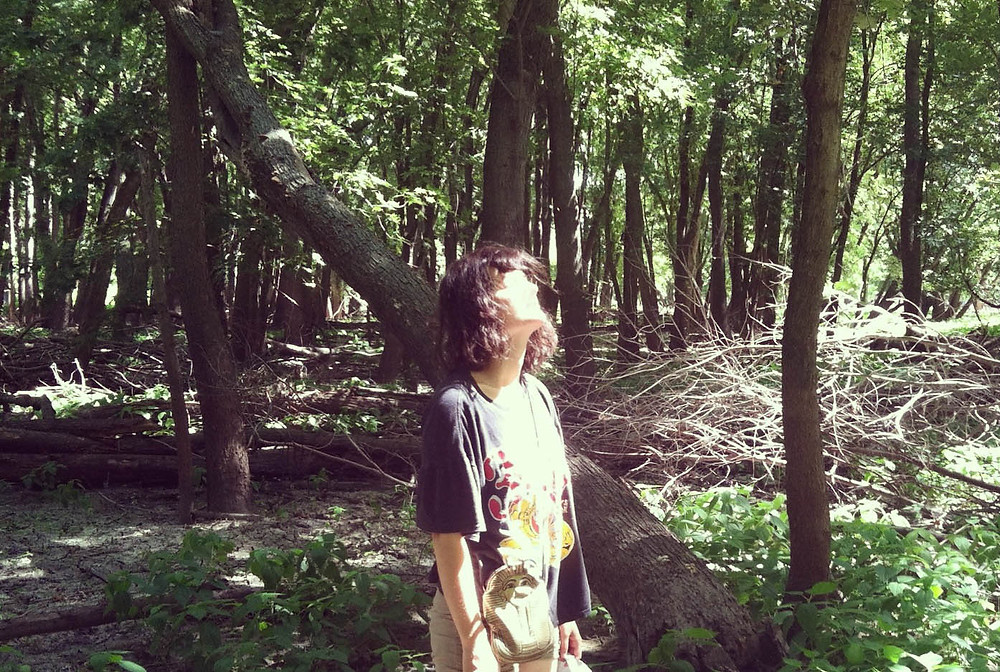 white woman looking at the sun while standing in the woods