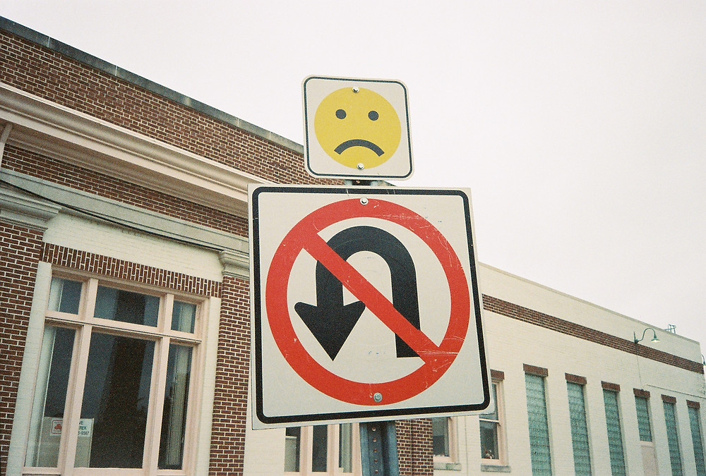 road sign for no u-turn with sign of frowny face above it