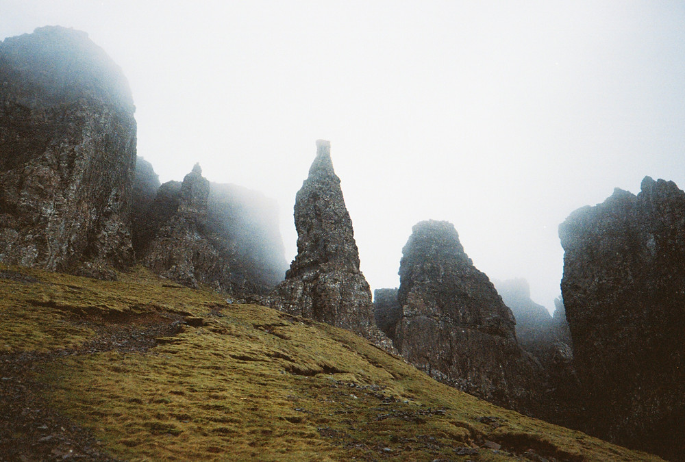 cloudy cliffs with rocks petruding and grassy ground