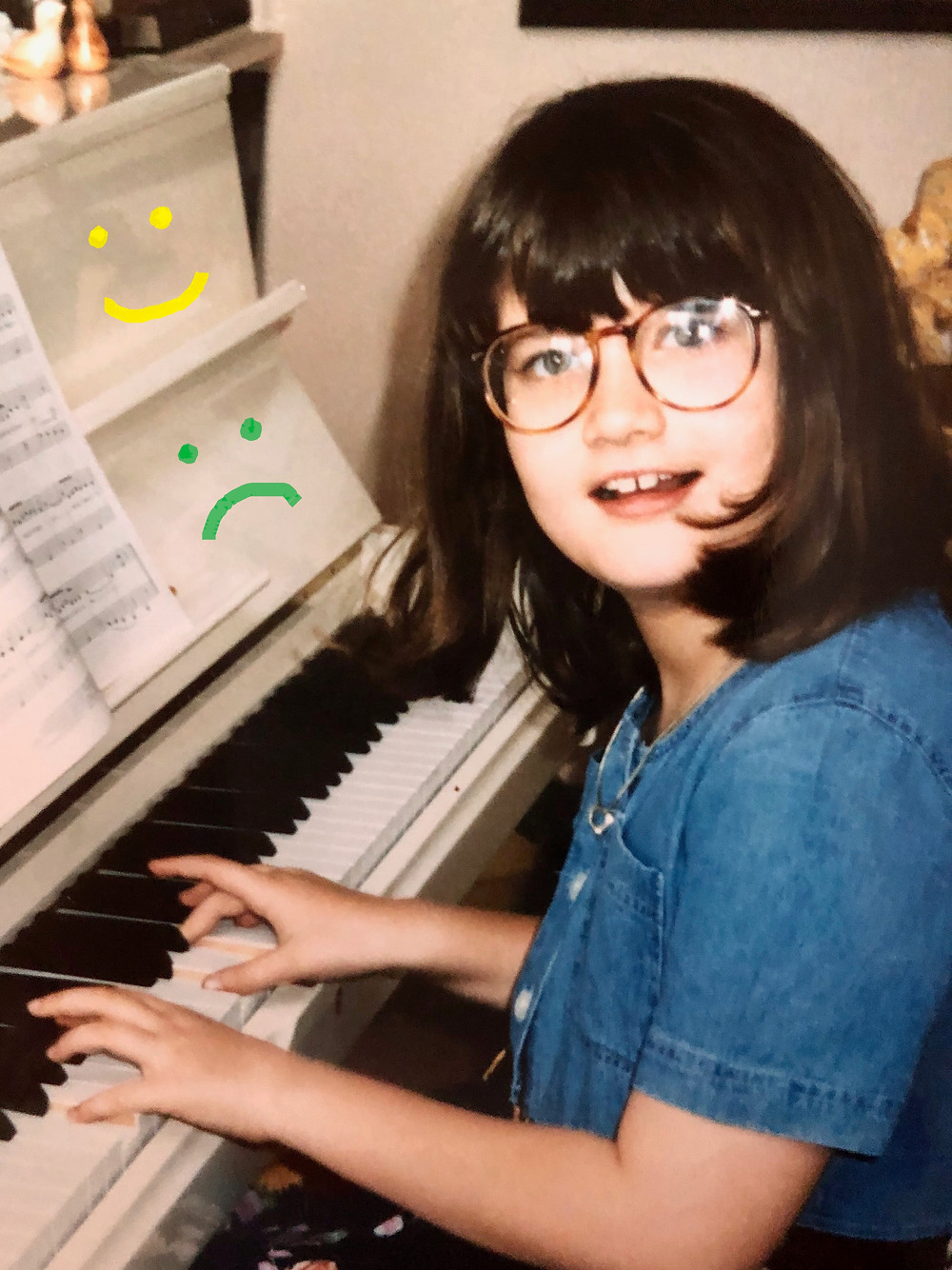 white girl with glasses and brown hair playing a white piano with handdrawn frowny faces on piano