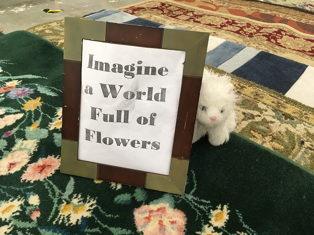 """small white stuffed animal sitting on floral rug, next to a sign that reads """"Imagine a World Full of Flowers"""""""
